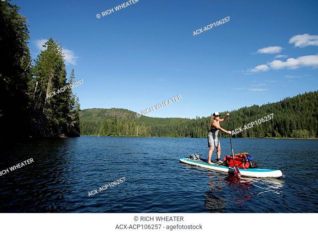 Stand-up paddleboard (SUP) touring in Main Lake Provincial Park, Quadra Island. British Columbia, Canada