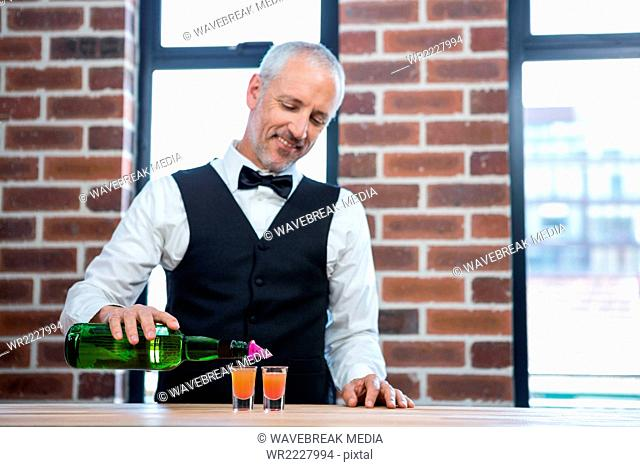 Barman pouring orange shots