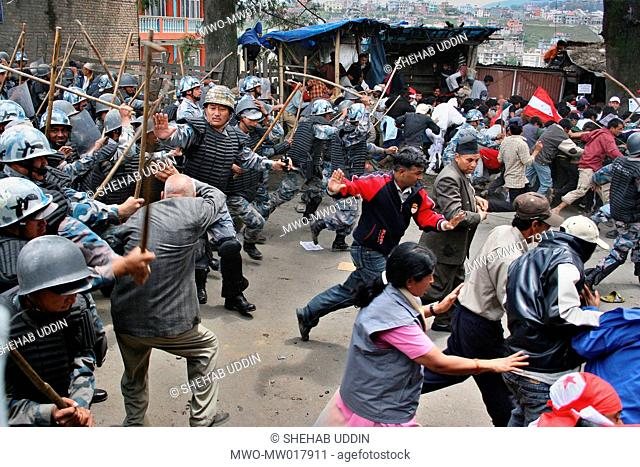 Police baton charge protesters during a demonstration in Katmandu, Nepal April 20, 2006 Nepalese police opened fire Thursday on tens of thousands of...