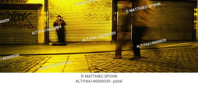 Musician leaning against roller shutter, people walking on cobble stone street, blurred motion