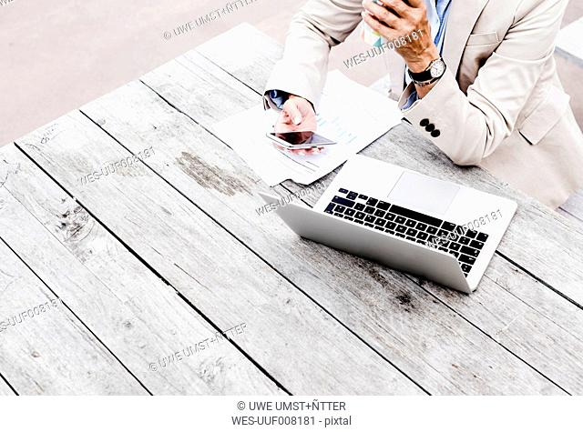 Businesswoman using smartphone while drinking coffee to go, partial view