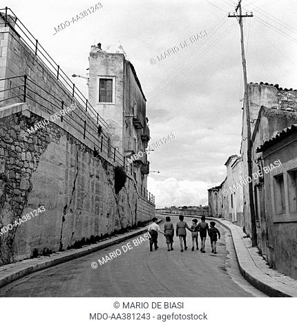 The neighbourhood called Ragusa Ibla . Some children walking hand in hand in the streets of the neighbourhood called Ragusa Ibla. Ragusa, 1955