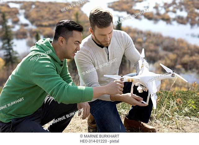 Male friends with drone on hilltop overlooking lake