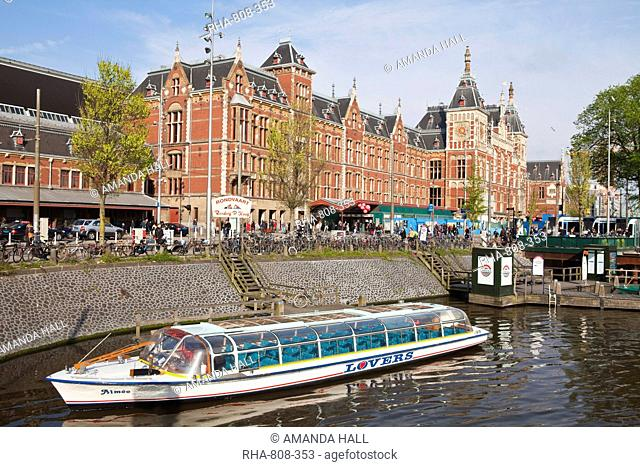 Canal tour boat outside Centraal Station, the central train station, Amsterdam, Netherlands, Europe