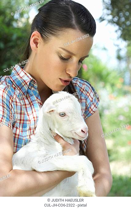 Young girl with goat in arm calming it