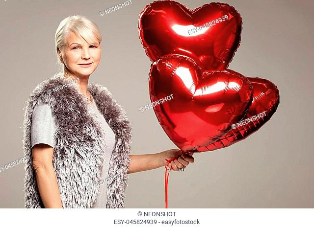 Elegant adult woman holding red balloons, valentine's day