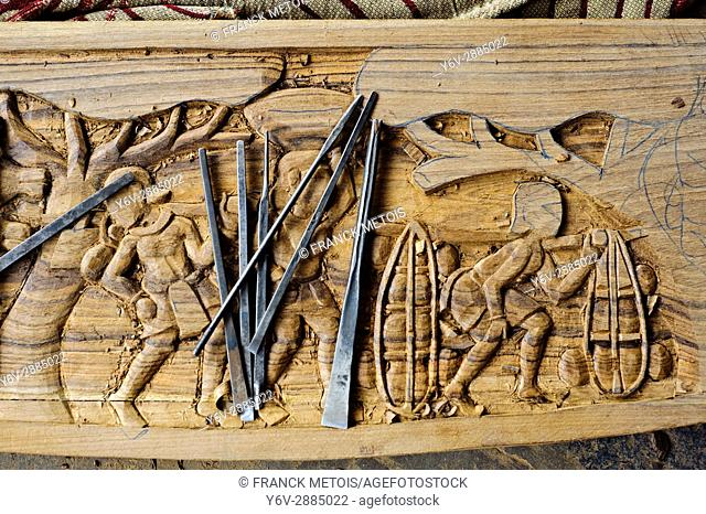 Ornate details on a wood table in a furniture workshop( Bastar region, India). The sculpture is representing tribal people