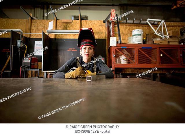 Portrait of female metalsmith at workshop bench