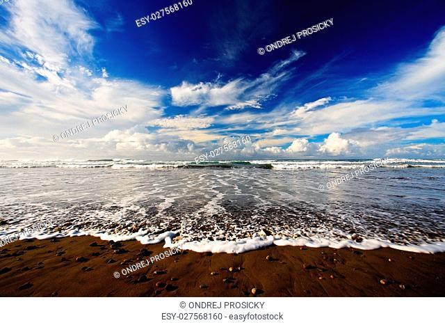 Beautiful sea landscape. The pebble and sand beach at sunrise