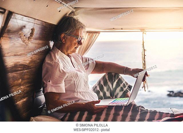 Senior woman sitting in vintage van by he sea, using laptop