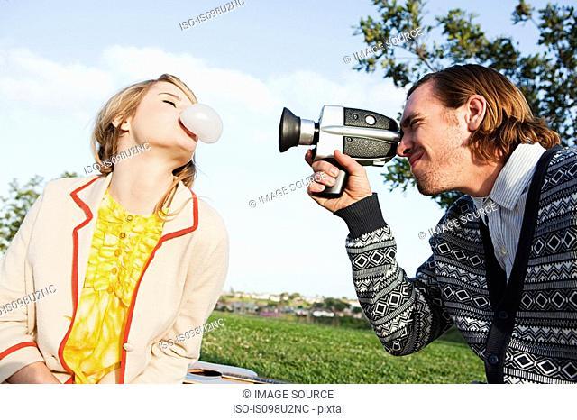Man filming girlfriend blowing bubble gum
