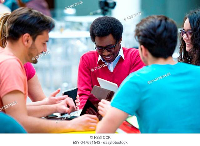 Multiracial group of young students studying together. High angle shot of young people sitting at the table and studying on laptop computer