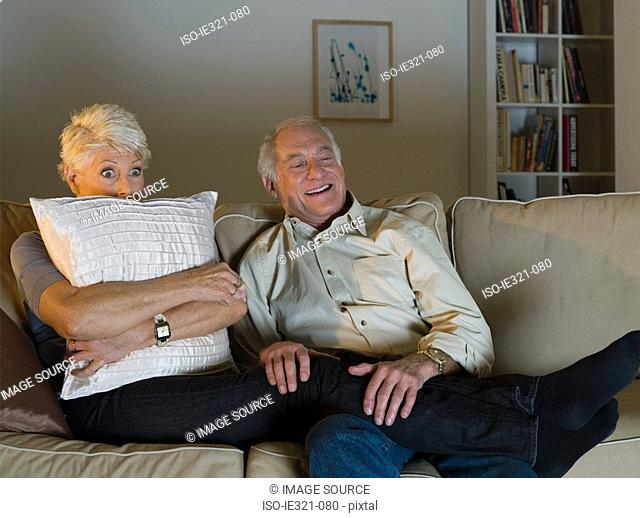 A senior couple watching tv