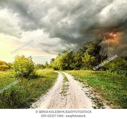 Country road through the forest and lightning