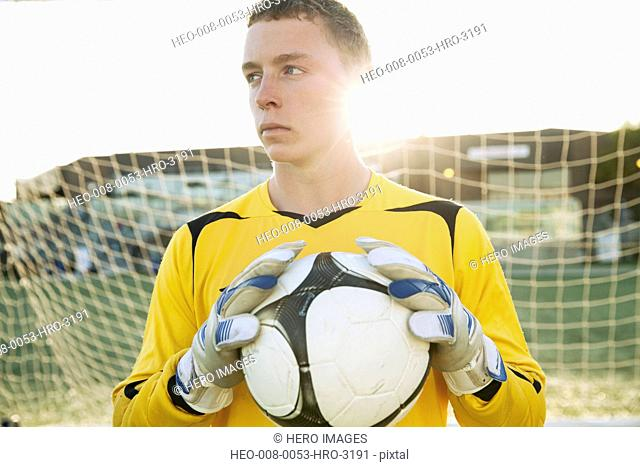 Soccer goalie with serious look holding soccer ball