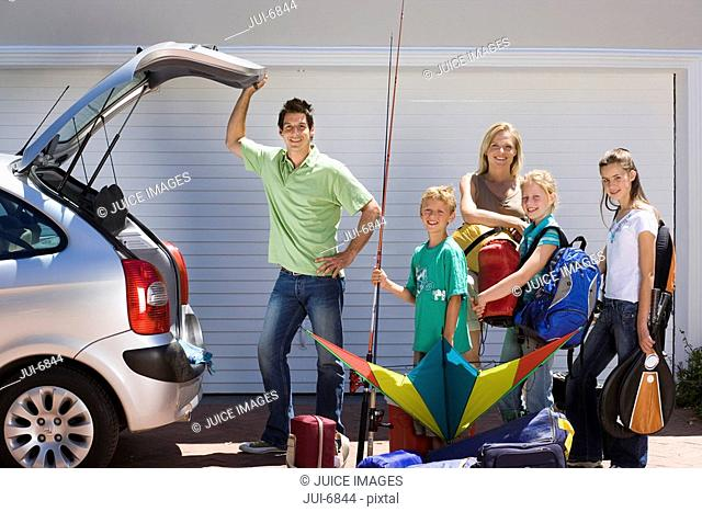 Family loading camping equipment into parked car boot on driveway, boy 8-10 holding fishing rod and kite, smiling, side view, portrait