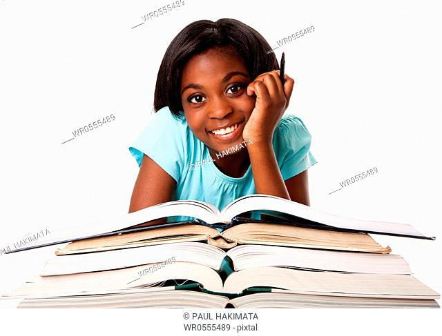 Beautiful happy smiling student with pen and a pile of open books doing homework, isolated