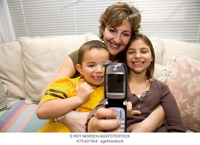 Mom holding two children and taking photo with camera phone