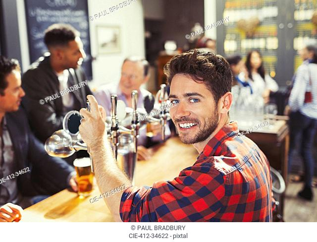Portrait smiling, confident male bartender serving beer at bar