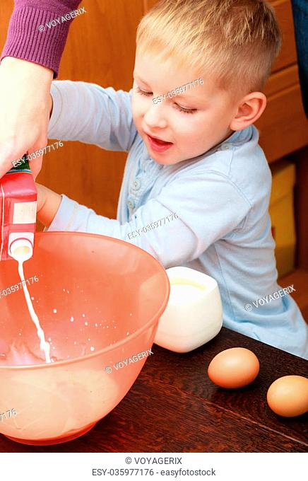 Happy childhood. Boy kid baking cake. Child preschooler pouring mik into a bowl. Kitchen. Real