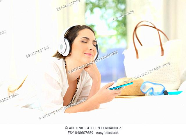 Candid woman listening to music relaxing in an hotel room on summer vacations