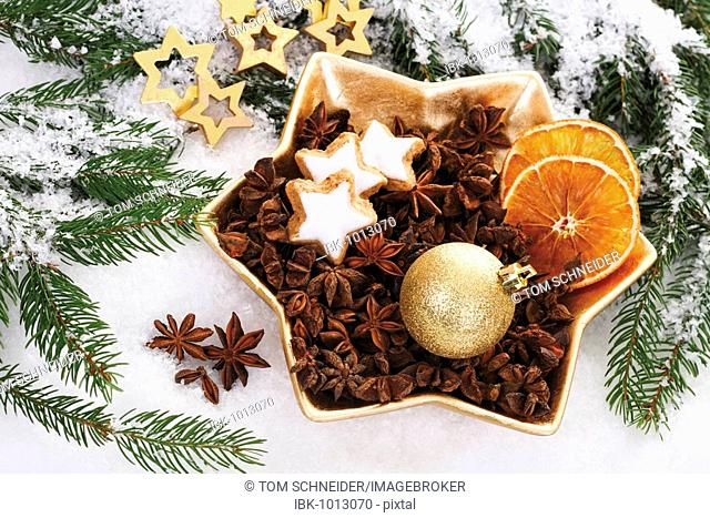 Christmas plate with star anise, cinnamon stars, a golden Christmas tree bauble and dried orange slices on branches of fir and snow