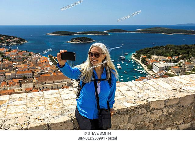 Caucasian woman posing for cell phone selfie with scenic view of ocean