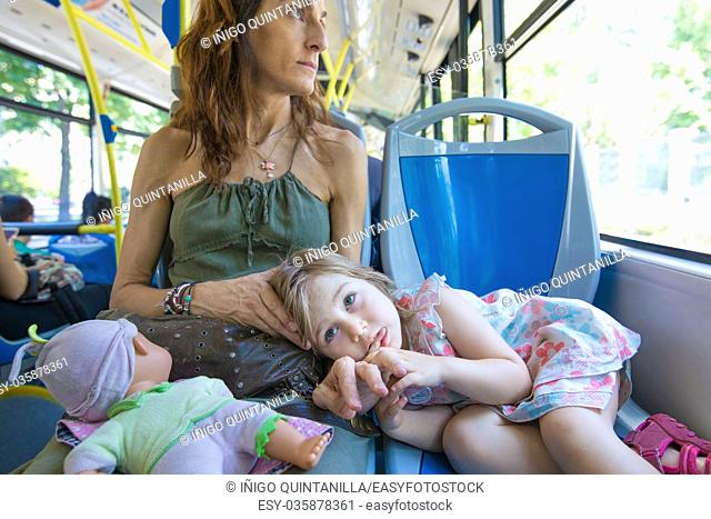 three years old blonde girl looking with doll lying on her mother legs sitting on the bus