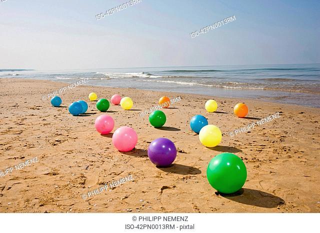 Colorful beach balls on sand