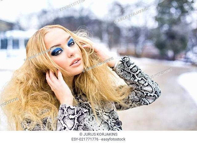 Golden haired woman posing outside