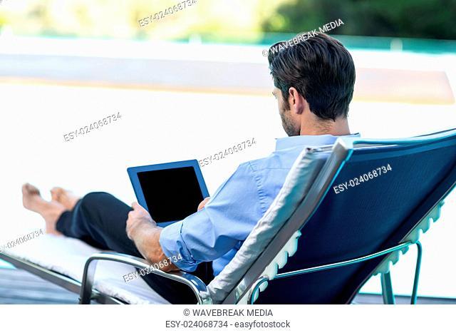 Man using digital tablet near pool