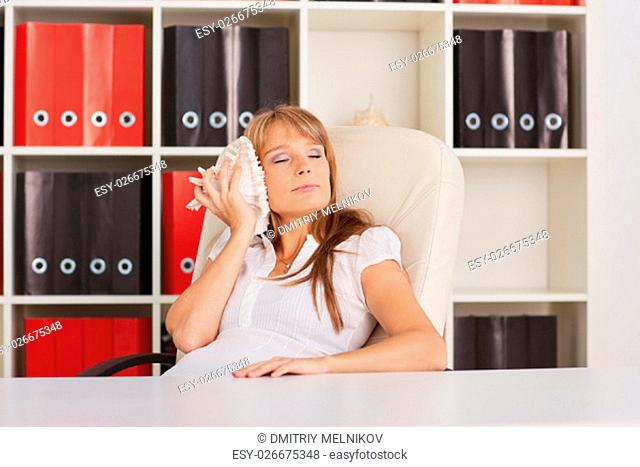 Young businesswoman rests at the table at the office. Timeout