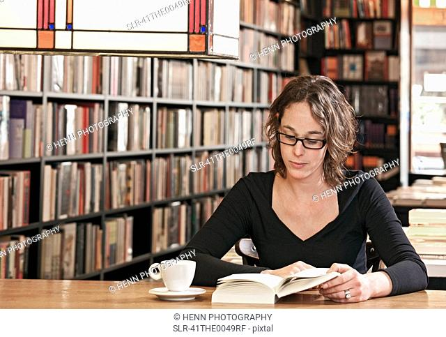 Woman reading in bookstore cafe