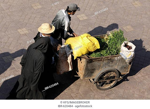 Men pushing cart loaded with raw green vegetables and sacks, Djemaa el Fna, Marrakech, Morocco, Africa