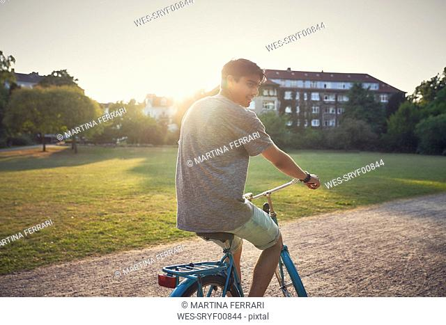 Young man riding bicycle in park