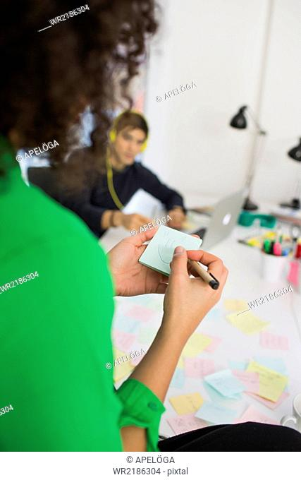 Cropped image of businesswoman making smiley face on adhesive note in office