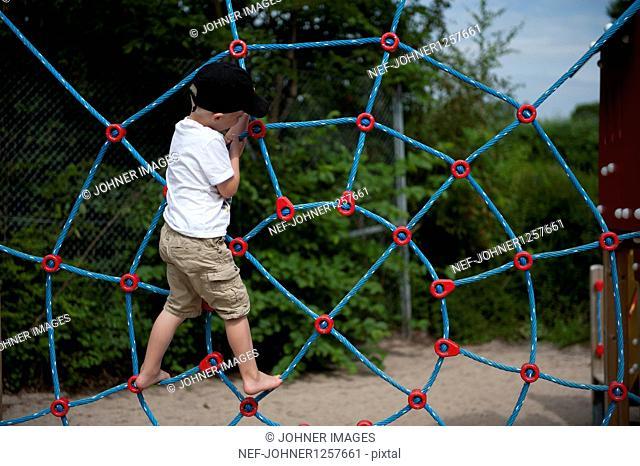 Boy climbing on net in playground