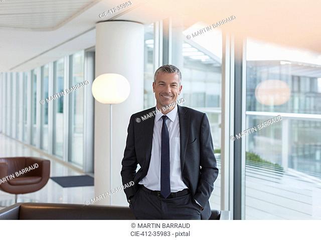 Portrait smiling businessman in office lounge