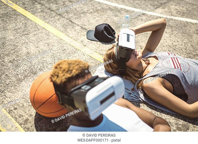 Young couple using virtual reality glasses, resting heads on basketball
