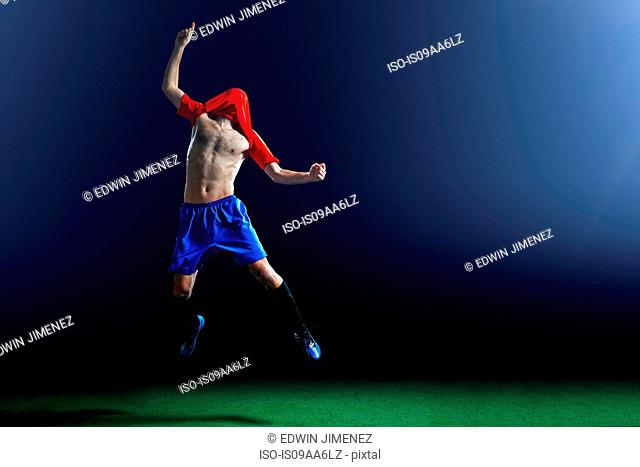 Male soccer player celebrating with shirt over head