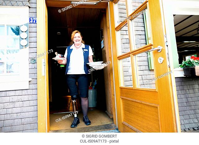 Mid adult woman with prosthetic leg, standing in doorway holding plates