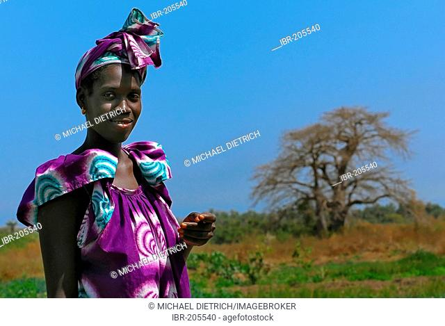 Young woman with Baobab tree in the background, near Tanji, the Gambia, Africa