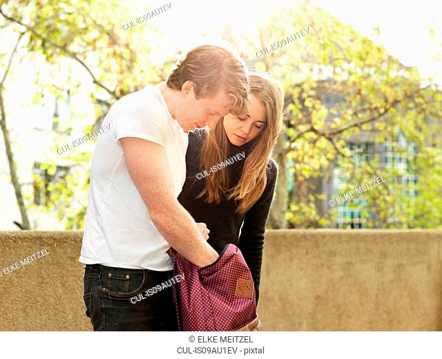 Young couple looking for something in bag, Melbourne, Victoria, Australia