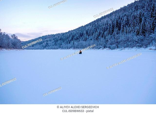 Landscape with distant view of man fishing on snow covered frozen lake
