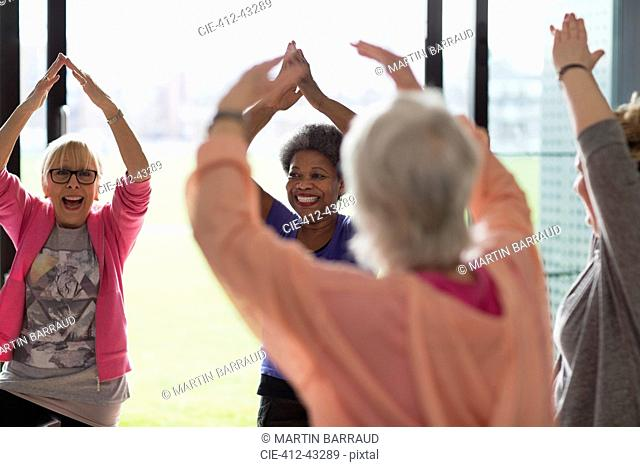 Happy active senior women exercising, stretching arms overhead in exercise class