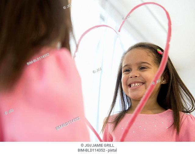 Hispanic girl making lipstick heart in mirror