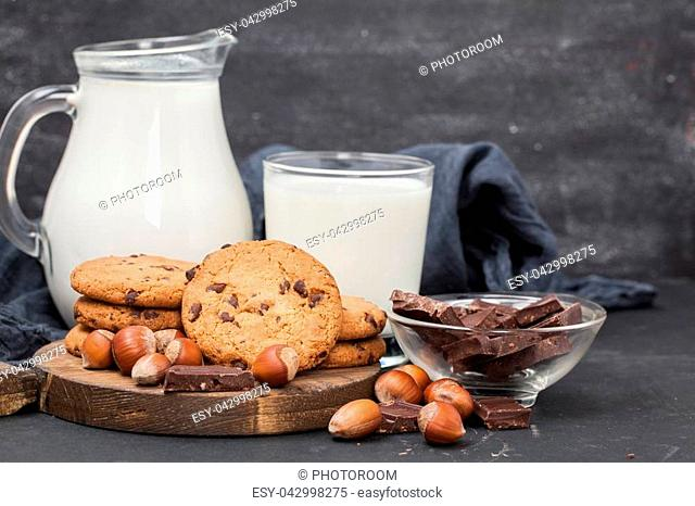 milk and chocolate cookie on wooden black background