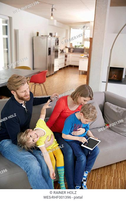 Family of four with digital tablet on couch