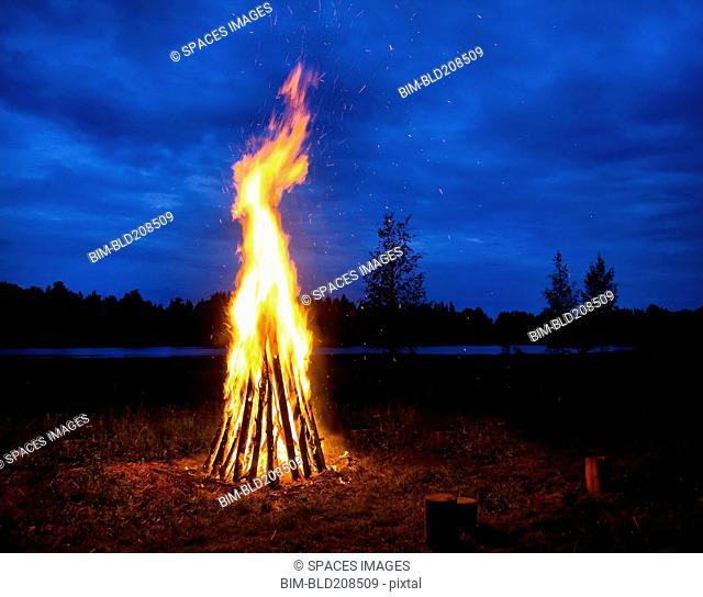 A tall bonfire with flames leaping up, at night