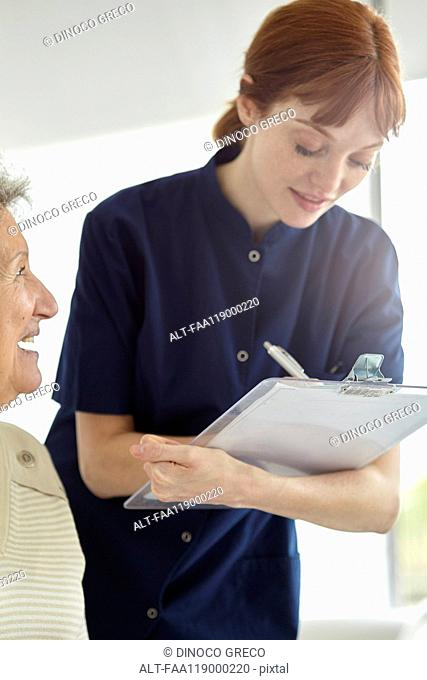 Nurse writing medical history of patient